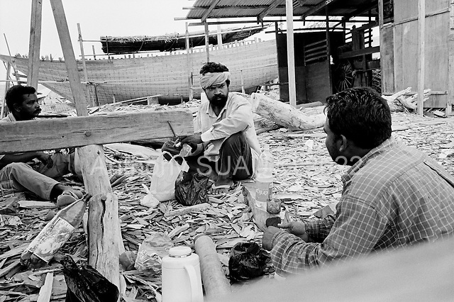 Sur, Oman<br /> July 2001<br /> <br /> Dhow builders break for a few minutes in the heat that often reaches 50 degrees centigrade (120 degrees Fahrenheit).