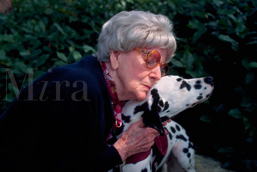 Elederly woman snuggles affectionately with a pet therapy dalmatian.