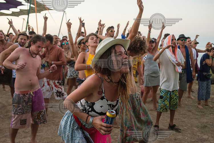 Youths dance at a music festival on the beach.