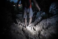 A pilgrim descends barefoot the Mt. Krizevac at night.<br /> Medjugorje, Bosnia and Herzegovina. July 2012