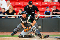 Catcher Dan Burkhart #15 of the Augusta GreenJackets tries to block the plate as home plate umpire Ramon Hernandez looks on during the South Atlantic League game against the Hickory Crawdads at L.P. Frans Stadium on April 29, 2011 in Hickory, North Carolina.   Photo by Brian Westerholt / Four Seam Images