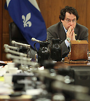 Bernard Drainville, PQ MNA for the riding of Marie-Victorin, joins hands as he listen to an answer from Pierre-Marc Johnson, representative of Quebec to the Canada-Europe free trade negotiations at the National Assembly in Quebec city, Thursday December 8, 2011.<br /> <br /> PHOTO :  Francis Vachon - Agence Quebec Presse