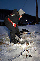 Young boy scoops poop in the early morning hours @ Takotna Chkpt 2006 Iditarod Interior Alaska Winter