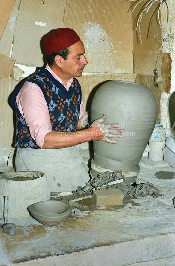 Tunisia, Nabeul.  Tunisian Potter at Work in his Workshop, wearing a chechia, the traditional Tunisian hat.