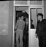 """Double crime d'Ondes. Les assassins keller et Horneich <br /> <br /> """"+ M. Dalas chef du SRPJ"""" 4 octobre 1972. Vue d'ensemble de face de Joseph Keller sortant des locaux de la police ou du Palais de Justice, menoté et entouré des policiers chargés de l'enquête. Cliché pris le lendemain de l'arrestation des deux suspects Joseph Keller et Marcellin Horneich dans l'affaire du double meurtre d'Ondes. Observation: Dans la nuit du 29 au 30 août 1972, un couple de touristes anglais autostoppeurs, est assassiné à Ondes (José Clive Latter 23 ans et Joy Joffe 20 ans). Un mois après, les auteurs du crime sont interpelés : ils s'agit de Marcellin Horneich et son neveu Joseph Keller. Ils avouent leur crime le 4 octobre 1972. Après 4 ans d'instruction, ils sont condamnés à mort le 25 juin 1976 par la Cour d'Assises de la Haute-Garonne. Le 8 janvier 1977, ils sont tous les deux graciés par le Président Valéry Giscard d'Estaing."""