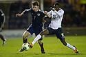 Scotland's Theo Archibald and England's Foday Nabay challenge for the ball.