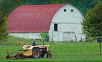 Farmer runs a cutter through a field as he makes his fourth  hay cut for the season on a small farm plot in Westerville, Ohio.<br />