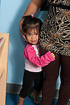 Education preschool visiting mother with shy toddler clinging to her leg (younger sibling of preschool age child)