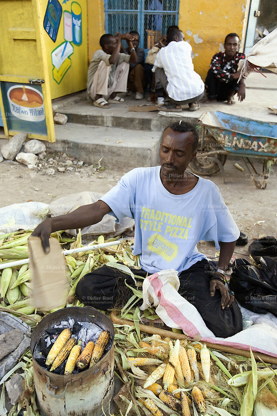 """Somaliland. Waqohi Galbed province. Hargeisa. A black muslim man,seated on the ground and wearing a blue te shirt with the words """"traditional style pizza"""", sells corns on the cob cooked on charcoal. Market stall. Somaliland is an unrecognized de facto sovereign state located in the Horn of Africa. Hargeisa is the capital of Somaliland. © 2006 Didier Ruef"""