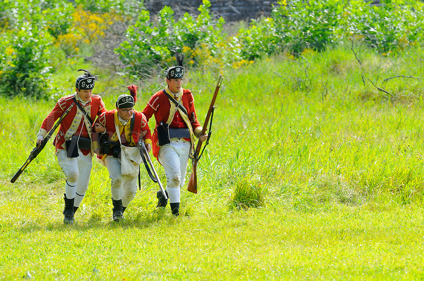 British redcoats of His Majesty's 20th Regiment of Foot rescue a soldier of the 29th Regiment during a Revolutionary War re-enactment at Fort Ticonderoga, New York, USA.