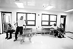 BEACON, NEW YORK-AUGUST: Andy (2nd L) and Tyrone escort  their puppies Rezzie and Happy to a medical facility to visit sick prisoners as part of the Puppies Behind Bars program. The patients look forward to the visits which are also used as a training exercise for the puppies who will work as service dogs. The program works with prison inmates in New York, New Jersey, and Connecticut to train both explosive detection dogs and service dogs, including ones who help injured soldiers or those suffering from post traumatic stress. Fishkill Correctional Facility is a medium security prison in New York with 22 men in the puppy program.