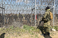 Pictured: A Greek soldier watches on as migrants walk behind the barb wired border. Sunday 01 March 2020<br /> Re: Clashes between migrants and riot police at the Greek-Turkish border of Kastanies near Evros, Greece