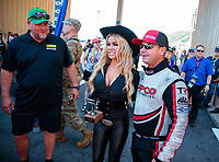 Jul 21, 2019; Morrison, CO, USA; NHRA top fuel driver Steve Torrence (right) poses for a photo with actress Carmen Electra as Richard Freeman looks on prior to the Mile High Nationals at Bandimere Speedway. Mandatory Credit: Mark J. Rebilas-USA TODAY Sports