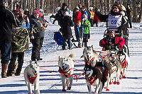 Karen Ramstead and team run past spectators on the bike/ski trail during the Anchorage ceremonial start during the 2014 Iditarod race.<br /> Photo by Britt Coon/IditarodPhotos.com