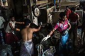 Workers offload raw hide while others process raw hides on a frizing machine at a tannery in the Bantala area of Kolkata, West Bengal, India.