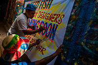 "A Colombian sign painter paints letters on a hand-painted promotional banner in the sign painting workshop in Cartagena, Colombia, 14 April 2018. Hidden in the dark, narrow alleys of Bazurto market, a group of dozen young men gathered around José Corredor (""Runner""), the master painter, produce every day hundreds of hand-painted posters. Although the vast majority of the production is designed for a cheap visual promotion of popular Champeta music parties, held every weekend around the city, Runner and his apprentices also create other graphic design artworks, based on brush lettering technique. Using simple brushes and bright paints, the artisanal workshop keeps the traditional sign painting art alive."