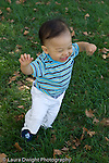 12 month old toddler boy walking on grass outside  vertical happy