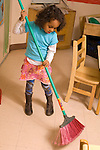 Preschool classroom New York City  classroom chore girl using broom to sweep floor vertical Hispanic American