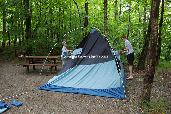 Two boys setting up a tent, Camden Hills State Park, Camden, Maine, USA