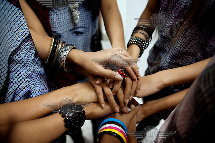 Members of 'Me N Ma Girls', Myanmar's first girl band, join hands before going on stage for a performance at a private function in a hotel in Yangon. The band's members were recruited by Australian dancer Nicole May. They sing and dance in the manner of many Western pop acts but in socially conservative Myanmar, they represent a radical break from the norm.