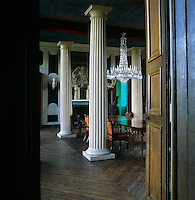 The dining room is characterised by four wooden columns with an 1830s English crystal chandelier above a Regency mahogany table