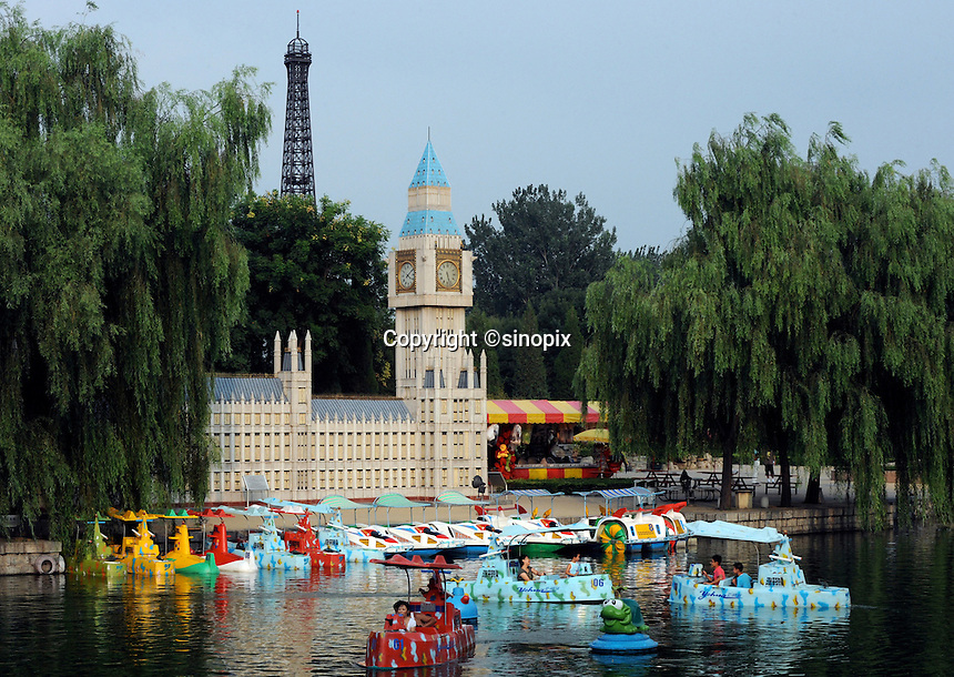 Families play on toy gun boats in front of a copy of the Houses of Parliament in world Park, Beijing. The park displays about 100 tourist attractions in a scaled-down version from nearly 50 countries around the world, including the Tower Bridge in London, the Eiffel tower in Paris, pyramids in Egypt, etc..16 Aug 2008