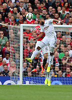 Pictured: Ashley Williams of Swansea (FRONT) heads the ball away from Wayne Rooney of Manchester United. Saturday 16 August 2014<br /> Re: Premier League Manchester United v Swansea City FC at the Old Trafford, Manchester, UK.