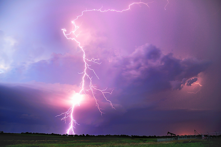 A cloud-to-ground lightning discharge arcs from the top of a supercell thunderstorm at dusk north of Winfield Kansas on June 16, 2009.
