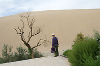 A worker in front of huge sand dunes at the tourist attraction Ming Sha Shan. Desertification is the process by which fertile land becomes desert, typically as a result of drought, deforestation, or inappropriate agriculture. Dunhuang, Gansu Province. China