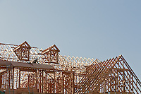 New Residential House Construction with wood framing and roof trusses and dormers against a blue sky