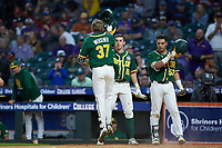Chase Wehsener (37) of the Baylor Bears is greeted at home plate by teammates Jared McKenzie (18) and Esteban Cardoza-Oquendo (52) after hitting a home run against the LSU Tigers in game five of the 2020 Shriners Hospitals for Children College Classic at Minute Maid Park on February 28, 2020 in Houston, Texas. The Bears defeated the Tigers 6-4. (Brian Westerholt/Four Seam Images)