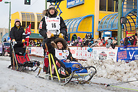 Joar Leifseth Ulsom and team leave the ceremonial start line with an Iditarider at 4th Avenue and D street in downtown Anchorage, Alaska during the 2015 Iditarod race. Photo by Jim Kohl/IditarodPhotos.com