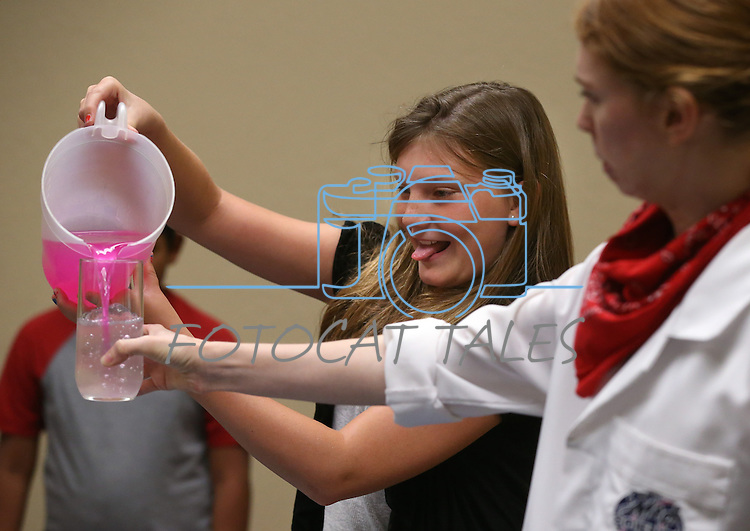 Emma Tuttle, 11, helps Radioactive Rachel with an experiment during the Mad Science program at the Carson City Library, in Carson City, Nev., on Tuesday, July 15, 2014.<br /> Photo by Cathleen Allison