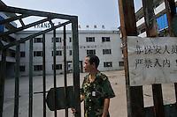 A security guard passes the closed factory gates belonging to Transit, one of several factories in Zhang Mutou in South China that went bankrupt in the current credit crisis. Transit produced handbags for western countries. Hundreds of factories in south China are closing due to increased labor and material costs and the current credit crissis is exasperating. The problem leaving ghost towns behind. .24 Oct 2008
