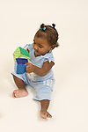 8 month old baby girl sitting full length playing with soft block toys banging them together vertical