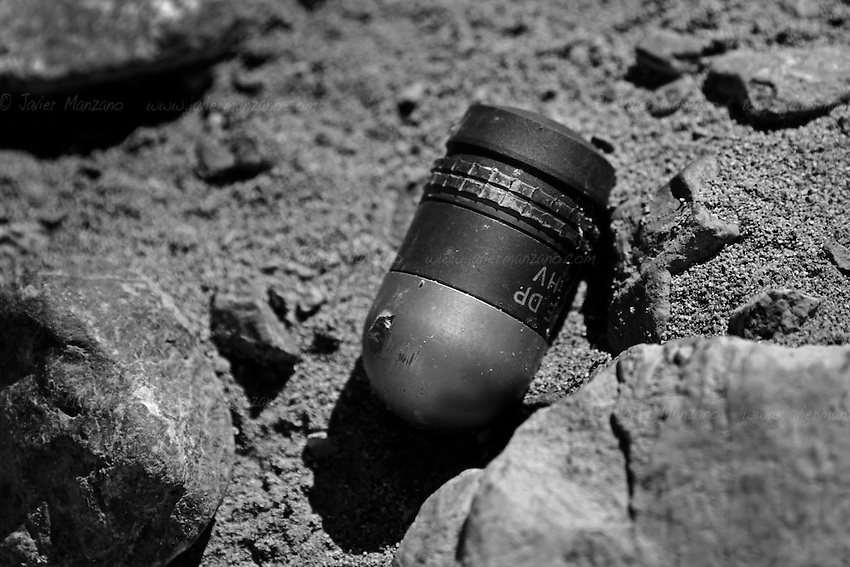 "PARWAN PROVINCE, AFGHANISTAN - MAY 19, 2012.  .A 40 mm live grenade lies on the sandy grounds of the East River Firing range in Bagram district. Even though this area is technically off-limits to the local villagers, there are no visible warning signs in Dari or Pashto, the two most prominent languages in Afghanistan. Moreover, the lack of adequate pasturing grounds for the local goat herders make it an economic necessity for them to cross over to the greener pastures that surround the firing range. ..In addition, what the local de-mining teams call ""scrappies"" - children who collect shrapnel and scrap metal to sell - walk into this firing range  to look for items such as rocket parts, bullet casings and other metal parts, are as a result, are being injured when they encounter live rounds (old soviet anti-personel mines and current 40 mm grenades used by the armed forces out of Bagram airbase when they conduct training on these grounds).  (Javier Manzano / For The Washington Post). .."