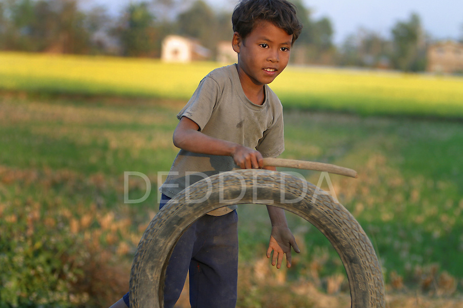 A young Nepalese boy plays with a stick and a tire on a rural road in Sauraha, near Chitwan National Park, in Nepal.