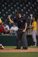 Home plate umpire Shin Koishizawa calls a strike during an Arizona League game between the AZL Athletics and the AZL Angels at Tempe Diablo Stadium on June 26, 2018 in Tempe, Arizona. The AZL Athletics defeated the AZL Angels 7-1. (Zachary Lucy/Four Seam Images)