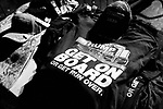 """MIDDLETOWN, PA — SEPTEMBER 26, 2020:  A T-Shirt reads """"get on board or get run over"""" at a rally for President Donald Trump during the Covid-19 pandemic at the Harrisburg International Airport on September 25, 2020 in Middletown, PA.  Thousands of attendees, most of whom were maskless, rode on shuttle busses to and from the long term parking lot and the event site— as the world nears one million Covid-19 deaths— defying the states ban on gatherings over 250 people.  Photograph by Michael Nagle"""