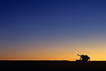 Silhouetted combine in field at sunrise getting ready to begin cutting wheat field, Eastern Washington State USA