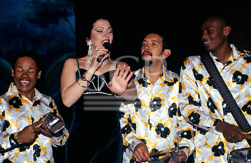 Sao Paulo, Brazil. Traditional folclore music show; woman singing in black dress, men playing in brightly coloured shirts