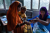 25 year old Dayawati (centre) takes a weekly supply of RUTF for her 17 month son, Naresh Mukhiya at the local health centre in Hanuman Nagar in Saptari, Nepal. <br /> Naresh Mukhiya was first admitted on July 17, 2013 when he was 9 months old. MUAC - 109 mm, Weight - 5.5kg, and Height - 65 cm. He was discharged on Oct 1st, 2013. MUAC at the time of discharge - 123, Weight - 6.5 Kg, Height - 66cm. Total RUTF consumes - 148 sachets.Gain of weight - 2gm.day.