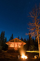 Rustic cabin and fire pit at night.