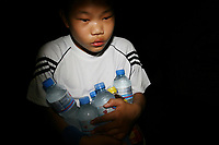 CHINA. Beijing. A young boy carries bottles of water whilst watching the opening ceremony of the Beijing Summer Olympics. 2008
