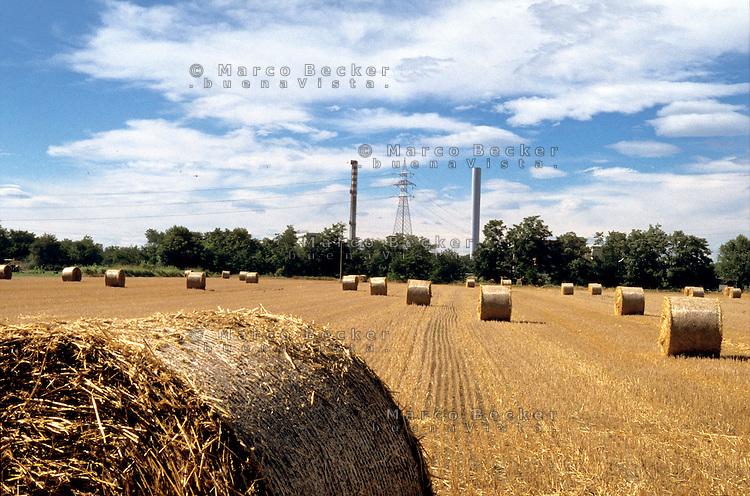 """Milano, località di Figino, periferia nord - ovest. Balle di fieno in un campo del Parco Agricolo Sud e sullo sfondo le ciminiere del termovalorizzatore """"Silla 2"""" dell'Amsa --- Milan, locality of Figino, north - west periphery. Hay bales in a field of the Rural Park South and on the background the chimneys of the incinerator and waste to energy plant """"Silla 2"""""""