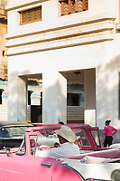 Man in vintage car on city street, Havana, Cuba