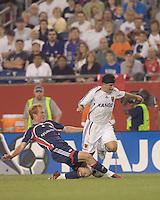 Jeff Larentowicz (Revolution, blue) with a hard tackle on Alecko Eskandarian (Real Salt Lake, white). New England Revolution played Real Salt Lake to a 0-0 tie, at Gillette Stadium on June 2, 2007.
