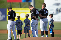 Danny Mendick (1), Johnathan Frebis (26), and Corey Zangari (14) of the Kannapolis Intimidators are joined on the field by three youth baseball players prior to the game against the Augusta GreenJackets at Intimidators Stadium on May 30, 2016 in Kannapolis, North Carolina.  The GreenJackets defeated the Intimidators 5-3.  (Brian Westerholt/Four Seam Images)