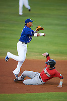 Biloxi Shuckers shortstop Orlando Arcia (2) throws to first over Danny Hayes (9) sliding in during a game against the Birmingham Barons on May 23, 2015 at Joe Davis Stadium in Huntsville, Alabama.  Birmingham defeated Biloxi 2-0 as the Shuckers are playing all games on the road, or neutral sites like their former home in Huntsville, until the teams new stadium is completed in early June.  (Mike Janes/Four Seam Images)