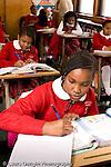 K-8 Parochial School Bronx New York Grade 4 girl writing in class vertical
